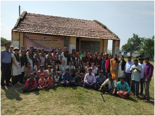 students and coordinators with villagers in front of School